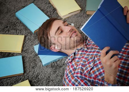 Concept of audiobook. Handsome young man with earphones and books lying on carpet
