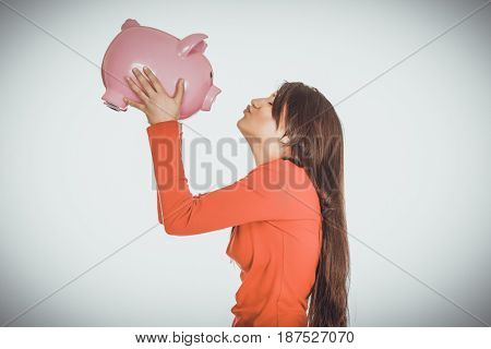Happy woman kissing her piggy bank.