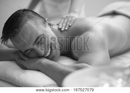 Positive young man having a back massage in a spa center
