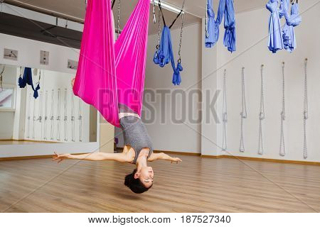 Girl in upside down pose on pink silk hammock with closed eyes meditation trying to rich harmony. Woman does aerial yoga exercises, meditates in position with straight legs. Aerial antigravity yoga.