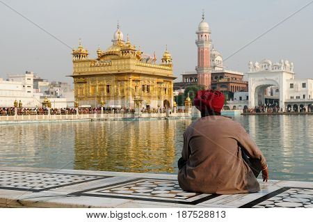The believer of the Sikhism is contemplating on the area of the Golden Temple.