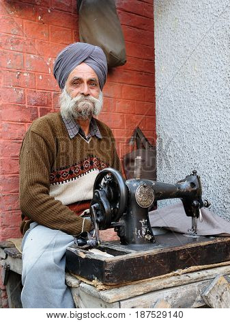 INDIA AMRITSAR - 02 DECEMBER 2009: Tailor with the sewing machine repairing clothes in streets of Indian cities