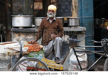 INDIA AMRITSAR - NOVEMBER 29: Rickshaw driver with one's rickshaw in the street of Indian city