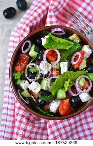 Classic Greek salad with sauce on a metal grunge background. Greek cuisine.