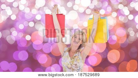 Digital composite of Happy woman with arms raised carrying shopping bags over bokeh