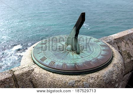 Antique Sundial On A Stone Wall Overlooking The Sea