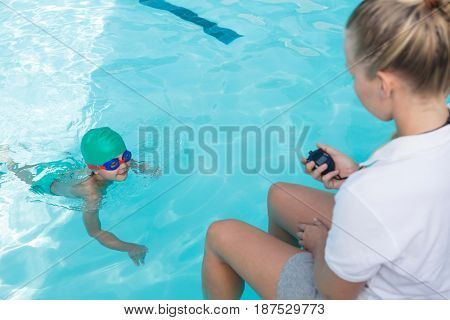 Female trainer monitoring time of boy swimming in pool at the leisure center