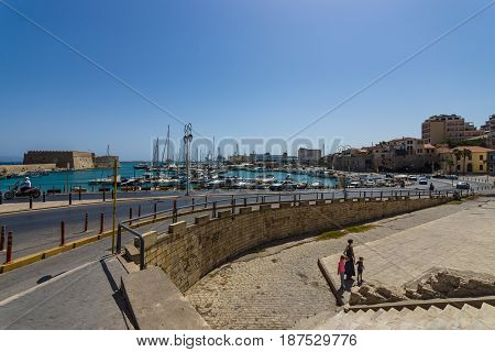 HERAKLION GREECE - JULY 16 2016: Crete. Moored fishing boats in the seaport. In the background an old Venetian fortress and the city's neighborhoods.