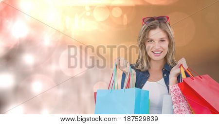 Digital composite of Portrait of woman with carrying shopping bags over bokeh