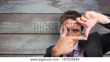 Digital composite of Businessman making finger frame against wooden wall