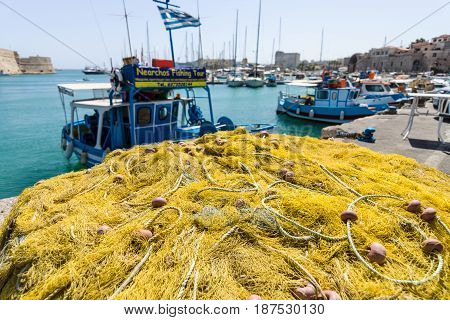 HERAKLION GREECE - JULY 16 2016: Crete. Fishing nets on the quayside. Moored fishing boats in the background.