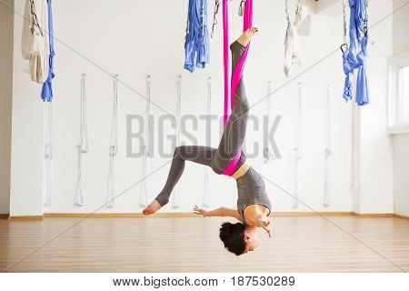 Star Inversion aerial antigravity yoga pose, woman do exercisese with hammock resting upside down with one leg covered by the material, hands gripping the sides, body slowly fall backwards