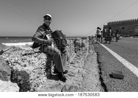 HERAKLION GREECE - JULY 16 2016: Crete. Musician on the waterfront plays accordion. In the background Venetian fortress. Black and white.