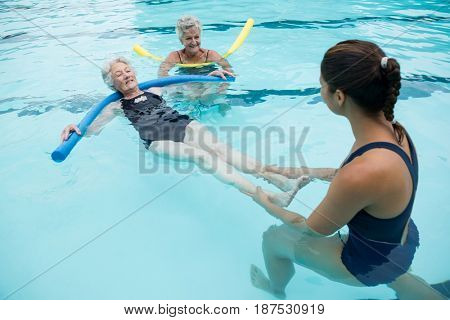 Smiling female coach helping senior woman in swimming pool