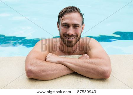 Portrait of smiling lifeguard leaning on poolside