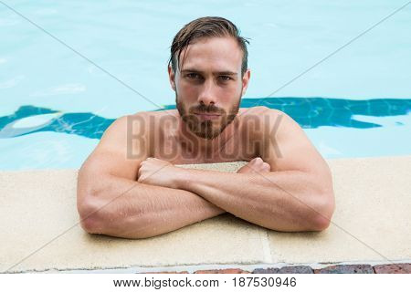 Portrait of lifeguard leaning on poolside