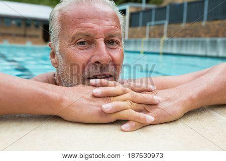 Portrait of senior man leaning on poolside