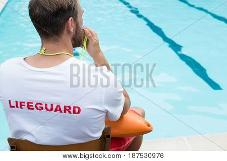 Rear view of lifeguard sitting on chair and blowing whistle at poolside
