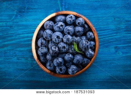 Fresh blueberry with drops of water in wooden bowl on blue  background. Top view. Concept of healthy and dieting eating