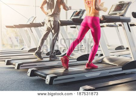 Male and female legs run on treadmills. Man and woman cardio workout in fitness club, crop. Healthy lifestyle, training in gym. Flare effect