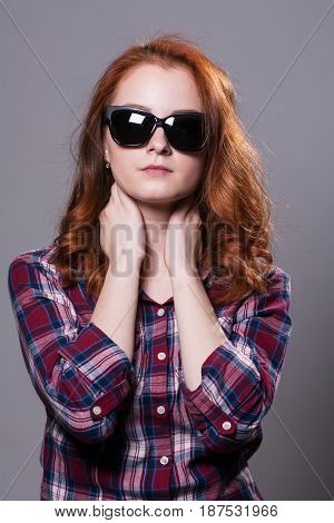 Portrait Of A Red-haired Beautiful Woman Wearing Sunglasses.