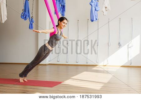 Adult woman practices aero anti-gravity yoga position in studio. Girl stretches back with help of hammock in gym, aerial yoga concept