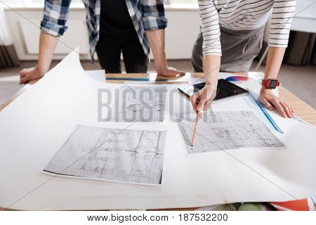 Engineering developments. Close up of several technical drawings lying on the table with nice hard working professional engineers standing around them