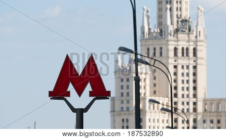 The symbol M is an underground metro in the background of Stalin's high-rise in Moscow