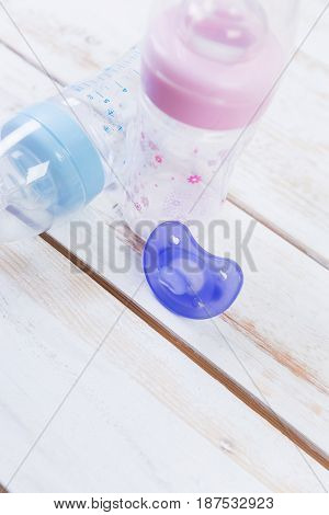 orthodontic pacifier on white wooden table .