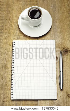 Notepad pen and cup of coffee on a wooden table