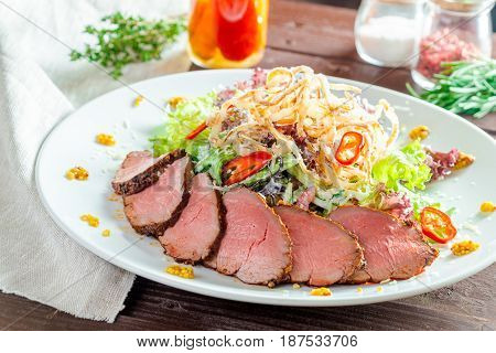 Fillet of beef with salad on the wooden table
