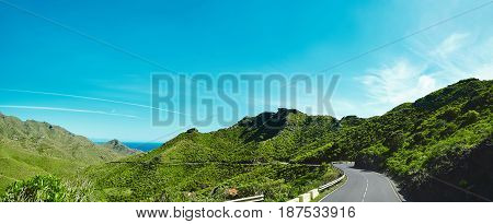 Panorama And Beautiful View Of Mountains And Blue Sky With Asphalt Road Is Meandering Between Blue F