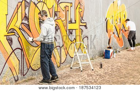 Urban street artists painting colorful graffiti on generic wall - Modern art concept with guys performing live murales with aerosol color spray - Focus on left person - Warm neutral filter