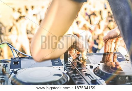 Close up of dj playing electro sound on modern cd usb player at summer beach party - Music festival and entertainment concept - Defocused background with shallow depth of field - Focus on mixing hand