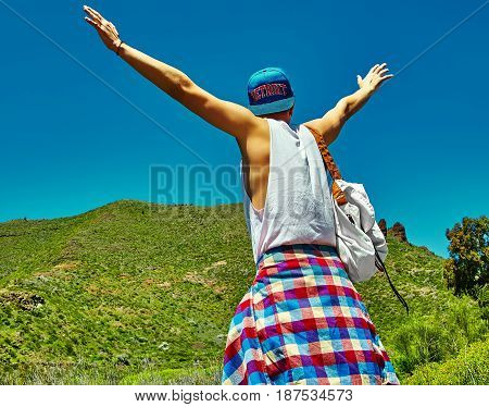 Happy Stylish Man In Casual Hipster Clothes Jumping In Front Of Mountain With Raised Hands To The Su