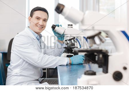 Positive thoughts. Young professional keeping smile on his face leaning on the table while putting left hand on the microscope