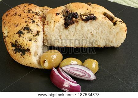 halved focaccia bun wit onions and olives