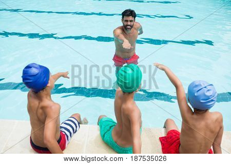 Coach and students taking oath in swimming pool at the leisure center