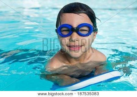 Portrait of smiling boy with swim goggles swimming in the pool