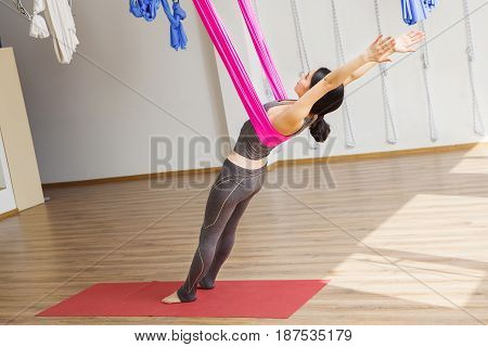 Girl leans back with help of hammock doing aerial yoga exercises in gym. Anti gravity position made with help of silk material. Building strength, enhancing flexibility, easing sore joints or muscles