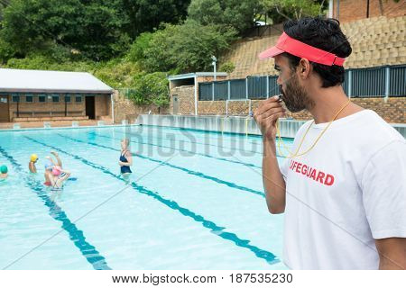 Lifeguard blowing whistle while students playing in pool on a sunny day