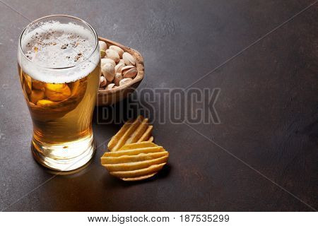 Lager beer and snacks on stone table. Nuts, chips. With copy space