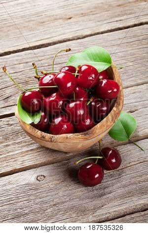 Fresh garden cherry in bowl on wooden table