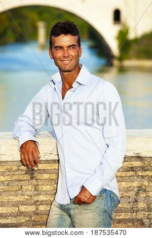 Beautiful smiling man outdoors. Tiber river from the bridge. A beautiful young Italian man posing outdoors on Milvian Bridge in the historic center of Rome, Italy. Blue shirt and jeans.