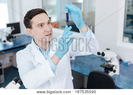 Something strange. Very attentive practitioner keeping his mouth opened and holding test-tube with blue liquid while examining it