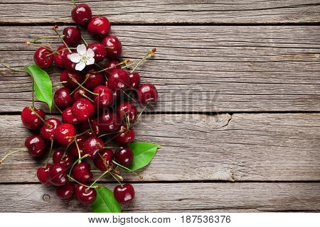 Fresh garden cherry on wooden table. Top view with copy space