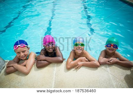Portrait of little swimmers leaning at poolside