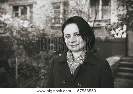 Portrait of an adult brunette woman in a trendy blue raincoat. She is standing in the street. Spring.