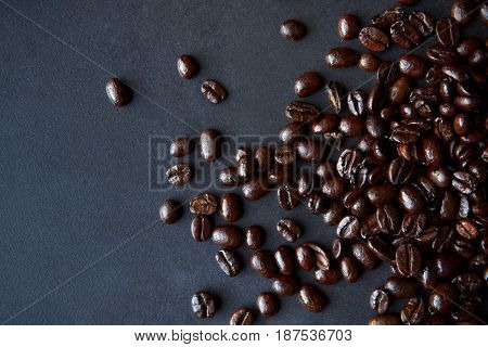 Roasted coffee beans on dark background, copy space