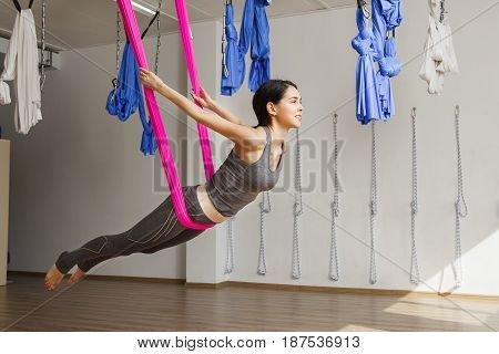 Adult woman practices inversion anti-gravity yoga position in gym. Aerial antigravity yoga girl on pink silk hammock, doing exercises, meditating in calm position of relaxed flying body